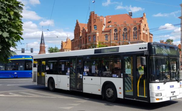 Na zdjęciu widać autobus miejski, w tle budynek Urzędu Miasta Torunia
