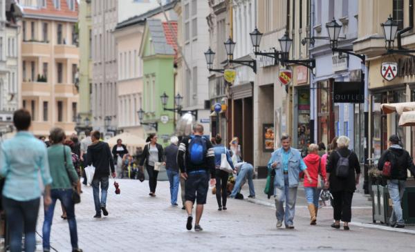 Na zdjęciu widać ludzi idących ulicą Szeroką