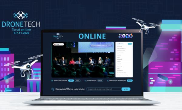 Laptop z widocznym na ekranie panelem dyskusyjnym ustawiony jest na tle plakatu zapowiadającego piątą edycję DroneTech Meeting