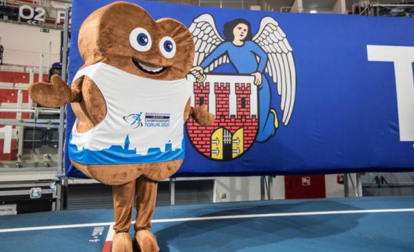 Na zdjęciu widac maskotkę Halowych Mistrzostw Europy w Lekkiejatletyce Toruń 2021 w kształcie katarzynki, w tle herb Torunia