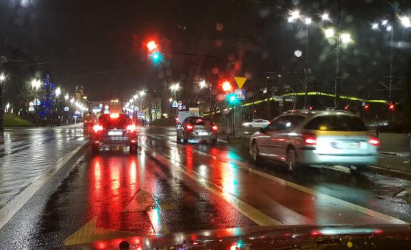 Na zdjęciu samochody stoją przed skrzyżowaniem, pada deszcz