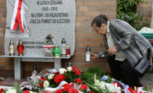 Kobieta pod tablicą Matki Polki Sybiraczki przy kościele na Koniuchach