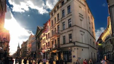 Zdjęcie przedstawia ludzi idących ulicą Szeroką.