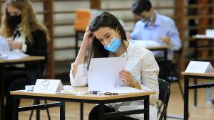 Uczennica w masce pochylona nad kartką papieru