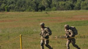Na zdjęciu widać dwóch żołnierzy biegnących z bronią po terenie poligonu