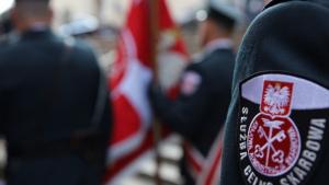 Na zdjęciu funkcjonariusze niosą sztandary, na pierwszym planie ramię mężczyzny w mundurze
