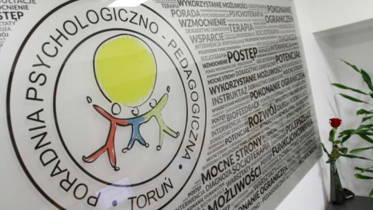 Na zdjęciu tablica z logo Poradni Psychologiczno-Pedagogicznej w Toruniu