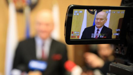 Prezydent Michał Zaleski w obiektywie kamery telewizyjnej przed mikrofonami dziennikarzy.