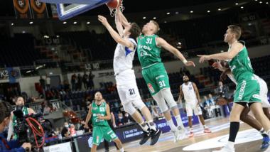 Na zdjęciu mecz koszykówki, zawodnik w białym stroju wrzuca piłkę do kosza