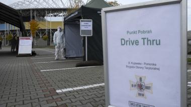 Na zdjęciu widać informację o punkcie pobrań typu drive thru oraz pracownika medycznego w kombinezonie ochronnym