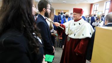 Na zdjęciu rektor AKSiM kładzie berło na ramieniu studenta
