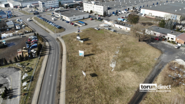 Na zdjęciu widać niezagospodarowany teren, w tle budynki usługowe, po lewej stronie ulica