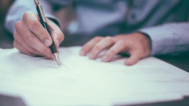 Grafika przedstawia dłonie trzymające długopis, którym podpisywane sa dokumenty