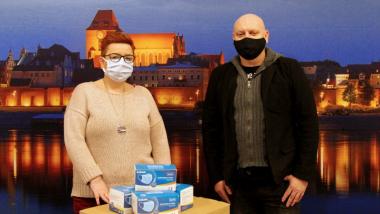 Na zdjęciu dyrektor Wydziału Promocji i Turystyki Ewa Banaszczuk-Kisiel oraz Arkadiusz Liczkowski z przekazanymi maseczkami
