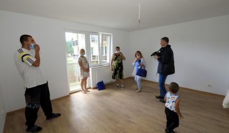 Na zdjęciu mieszkańcy przyglądają się mieszkaniom