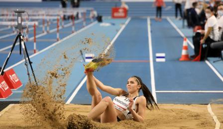 Zawodniczka ląduje w piasku po skoku w dal.