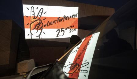 flaga wolnej Białorusi odbijająca się w szybie samochodu