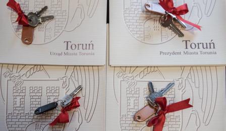 """Na czterech teczkachz napisem """"Toruń. urząd Miasta Torunia"""" leżą cztery klucze do mieszkań z przywiązaną czerwoną wstążką"""
