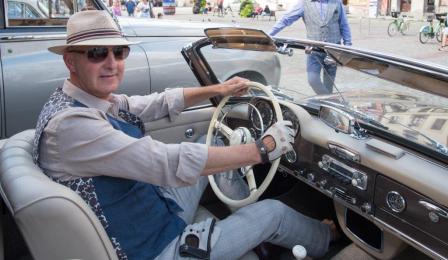 Na zdjęciu: mężczyzna za kierownicą zabytkowego auta