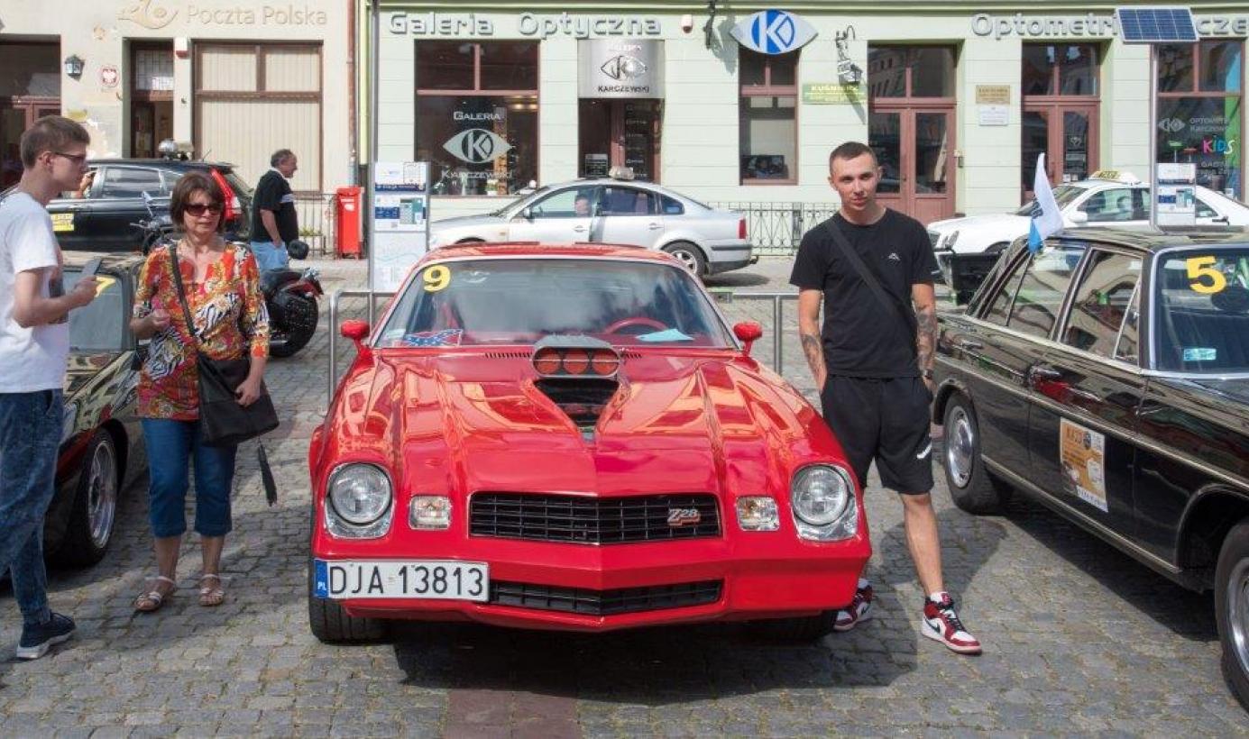 Na zdjęciu: czerwony samochód i osoby oglądające