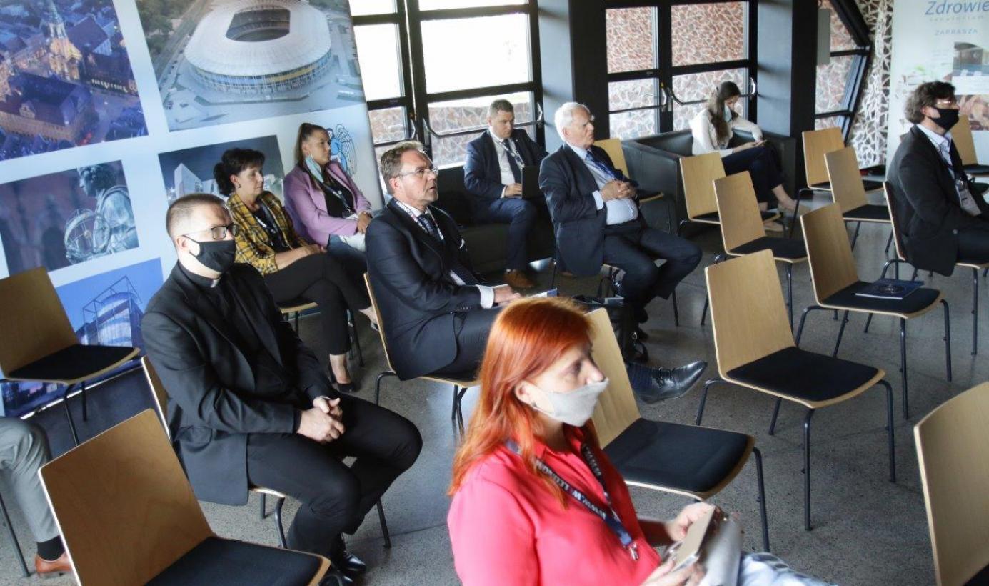 Na zdjęciu widac osoby przysłuchujące się debacie, wszyscy mają usta i nos zakryte maseczkami